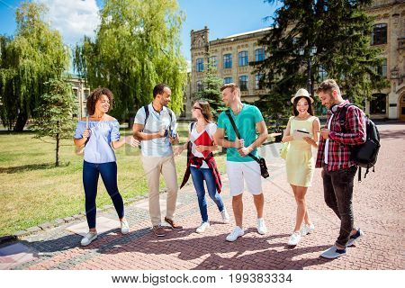 Free time of a students bachelor`s campus life rhythm. Six friendly students are walking after they passed test outside the college building and discuss the project smiling enjoying carefree