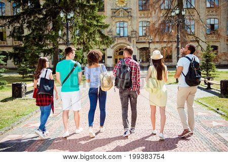 Rear View Of Six Students, Bachelor`s Campus Life Rhythm. They Are Walking After To College Building