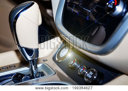 Engine start and stop button in a modern and luxury car. Black leather interior in a modern vehicle.