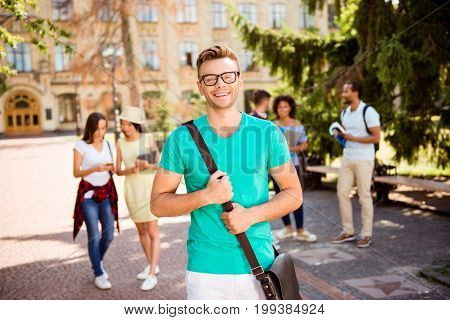 Young successful blond nerdy student is standing with bag and smiles behind are his classmates park near campus sunny day carefree and enjoyable mood