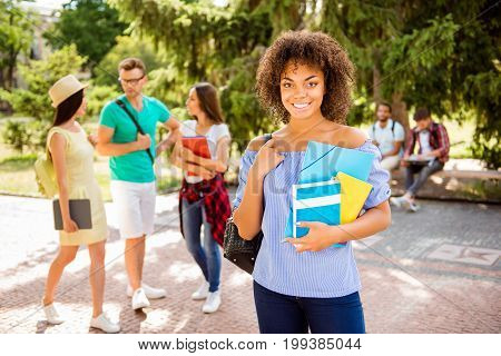Portrait of an attractive young mulatto student standing with rucsack and note pads with beaming smile behind are her friends talking outside in a sunny park near college