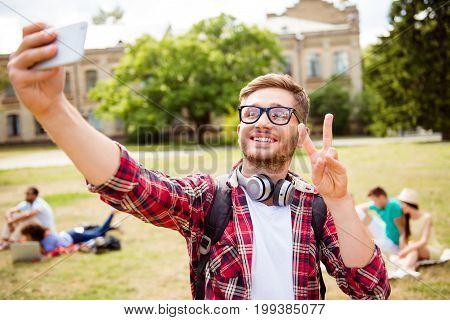 Peace to all! Young goofy blond nerdy student in checkered shirt is taking selfie shot behind are his classmates park near campus sunny day carefree and enjoyable mood