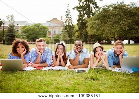 It`s more easy together! Six cheerful classmates are lying down on plaid on the green grass in spring sunny park near campus and study preparing for exams tests with book notepads laptops tablets