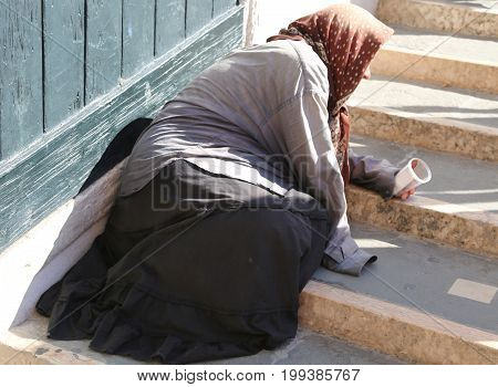 gypsy woman with headscarves on her head and long skirt asks alms to people on the grand staircase