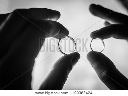 wedding rings in hands of the groom and