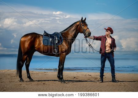 Macho man handsome cowboy with amazing muscles and abs and horse are on the background of sky and water. Western style