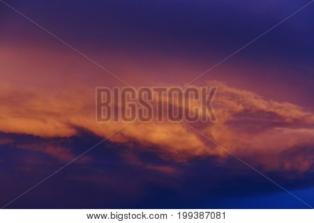 pink orange sunset clouds with purple and deep blue shadows in the sky