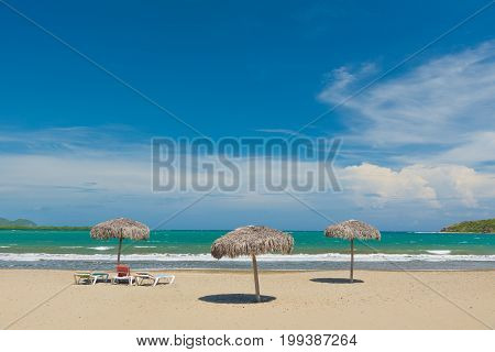Idyllic sand beach with beach umbrellas and chairs. Caribbean Sea. Cuba