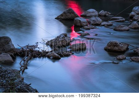 Dark river flowing over the rocks and dry tree branches with red glow reflecting. Environmental destruction, ecology, climate change conceptual background
