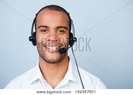 Young Cheerful African Guy Call Center Worker In Headset On A Pure Light Background, Wearing Headset