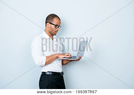 Confident Pensive Young Mulatto Americano Market Broker Is Looking At His Laptop, Standing On The Pu