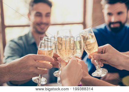 Close up of friends cliking the glasses of bubbling champaigne to celebrate special occasion together