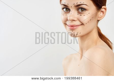 Young beautiful woman on a light background with a contour on the face, plastic surgery, operation, empty space for copy.