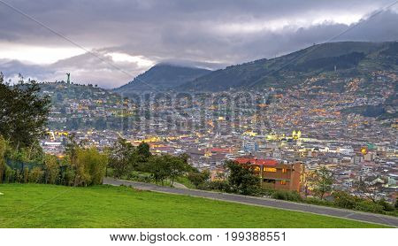 Panorama of the city of Quito, it's downtown area, the Panecillo hill and the Ecuadorian Andes mountain range, on a cloudy day. Late afternoon. Quito, Pichincha, Ecuador.
