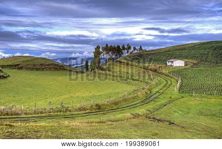 View of a house, a road and a green mountain range, part of the Ecuadorian Andes, with a beautiful sunny and cloudy sky. Cayambe, Ecuador.