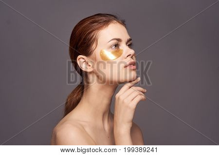 Young beautiful woman in gold patches for eyes on a black background, portrait, facial treatment.