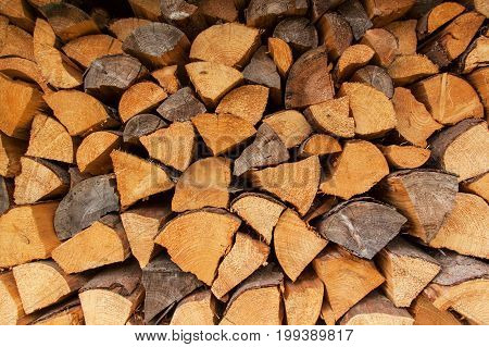 Timber stock for winter. Dry logs of wood in the background. Sale of wood