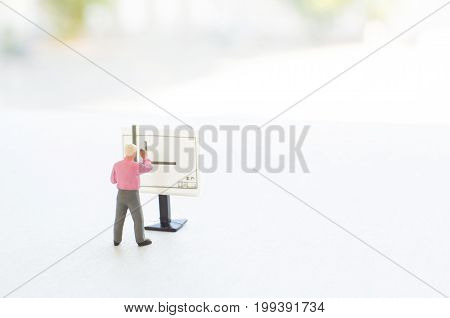 A conceptual photo with a toy engineer or other professional  at the empty drawing board with a place for your text. Focus on a figurine of a human.