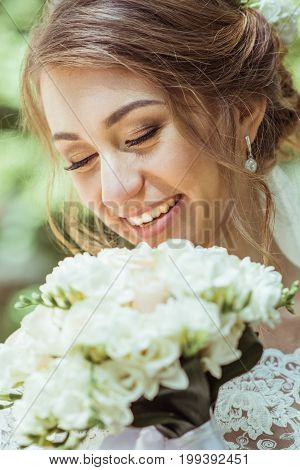 Close up portrait of bride holding wedding bouquet. Bride walking with a wedding bouquet in the summer park. Woman with a bouquet. Toned