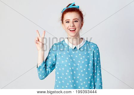 Happiness beautiful redhead girl shows peace or victory sign. Isolated studio shot on gray background.