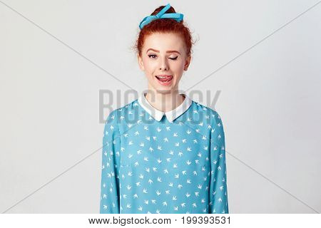 Young teenage girl with ginger hair knot sticking out her tongue having funny look isolated over gray background. Studio shot.