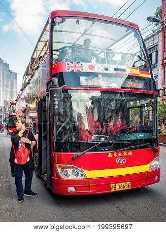 Shanghai, China - Nov 6, 2016: City sightseeing double-decker bus boarding passengers near the 600-year-old Old City God Temple on Fangbang Middle Road. A popular way to see the city.