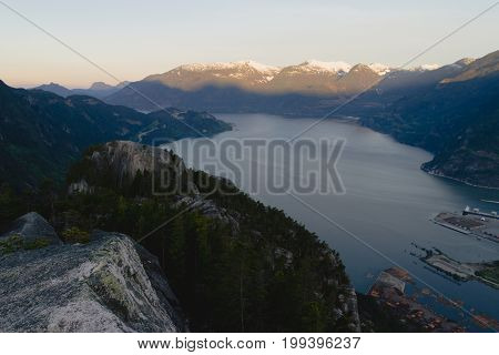Man In Sleeping Bag On The Top Of Mountains Above Lake While Sunrise