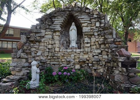 JOLIET, ILLINOIS / UNITED STATES - JULY 17, 2017: A grotto display, featuring a sculpture of the Virgin Mary, stands on the Quad at the University of Saint Francis.