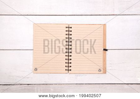 Notebook recycled paper blank on wood table.