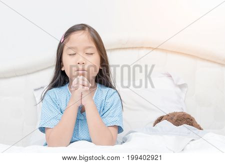 Little girl praying on bed. Little asian girl hand praying Hands folded in prayer concept for faithspirituality and religion.