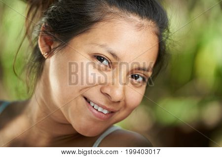 Headshot of smiling with teeth hispanic girl on blurred background
