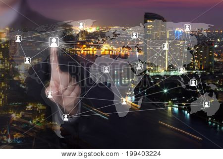 A Businessman using his finger pressing social network icon with blurred background of big city.