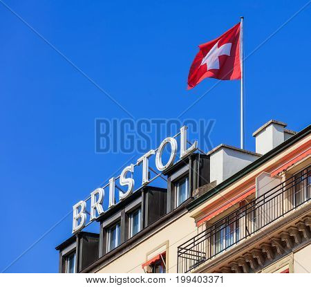 Geneva, Switzerland - 24 September, 2016: sign and flag of Switzerland on the roof of the Hotel Bristol Geneva in the city of Geneva. Hotel Bristol Geneva is a 4-star hotel, located only 1.8 km from United Nations Geneva and PalExpo.
