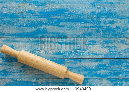 Wooden Rolling Pin On Blue Wooden Table. Top View