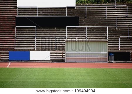 Seating of a grandstand behind a coach bench in a soccer stadium.