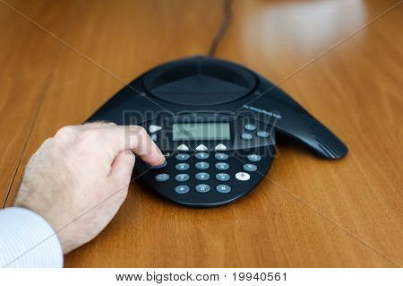Businessman Dialing On Conference Phone