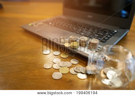 coins on computer and on the table , concept save money , save money for the future