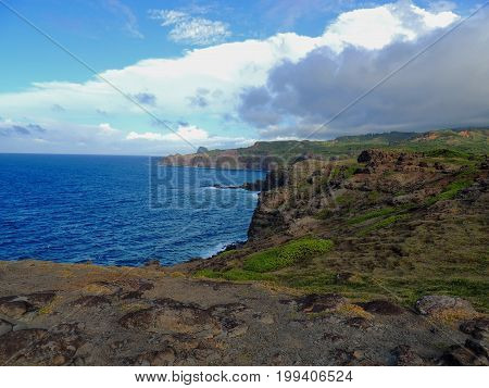 Rough and rocky shore, blue ocean and clouds at north-west coast of Maui, Hawaii, USA
