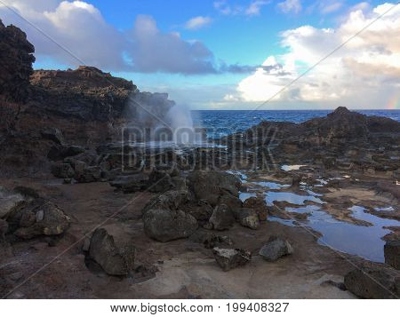 Nakalele Blowhole with water spraying out with ocean and sky in the background, it was created from Pacific Ocean waves hitting the tall rocky cliff coastline that was created from lava on Maui, Hawaii, USA sky reflecting off the still water