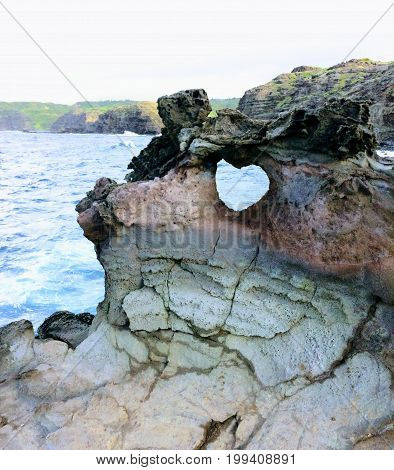Heart shape geological formation naturally occurring in lava rock wall at Nakalele in Hawaii, USA, with ocean and Maui Mountains in the background landscape with splashing waves