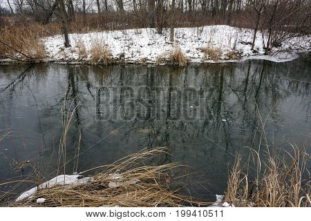 Ice begins to form on the surface of a quarry pond in the Rock Run Preserve of Joliet, Illinois, during January.