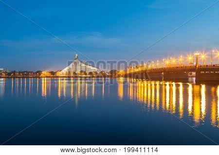 Latvian national library and stone bridge over Daugava river in Riga. Night illuminated scene.