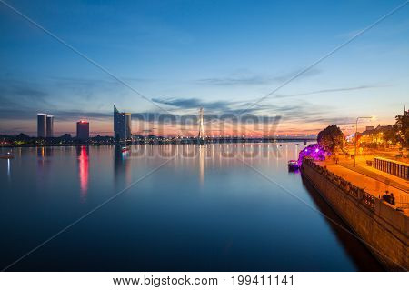 Deep sunset panoramic scene over Daugava river in Riga, Latvia. New business buildings on the left and old town on the right.