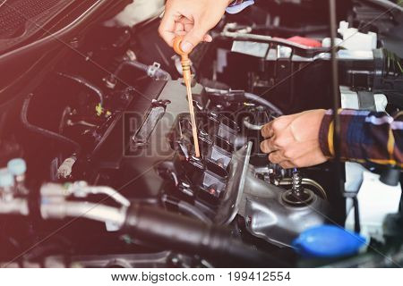 Close up hands checking lube oil level of car engine from deep-stick for service and maintenance concept vintage tone.