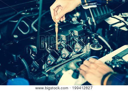 Close up hands checking lube oil level of car engine from deep-stick for service and maintenance concept.