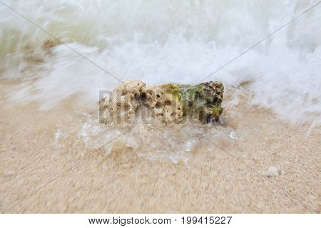 Abstract Blurry Background Of Coral On Sandy Beach With Soft Waves And Beach Waves.