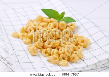 pile of honey cereal rings on checkered dishtowel - close up
