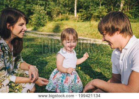 young parents play with her daughter outside