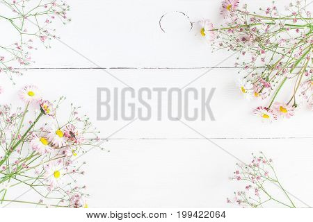 Flowers composition. Floral frame made of pink gypsophila flowers and daisy flowers on white wooden background. Flat lay top view copy space