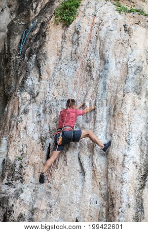 Tourist Man Climbing On A Limestone Wall On Krabi Province At Thailand.